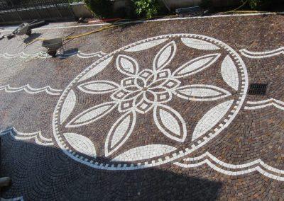 Pavimento in cubetti di porfido con decorazione.